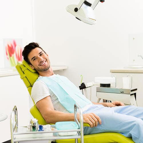 A young man lying in the green chair of the dentist, while smiling and wearing a white shirt