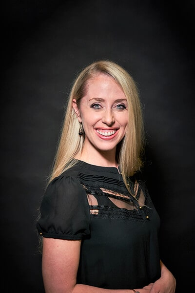 Dr. Elisabeth Easley, standing wearing a black shirt with gold trimmings and long earrings, smiling directly with her blond hair and blue eyes.