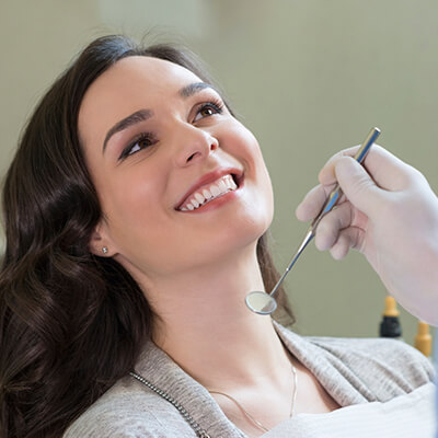 A woman in the office sitting and smiling while the dentist holds a dental instrument in her hand.