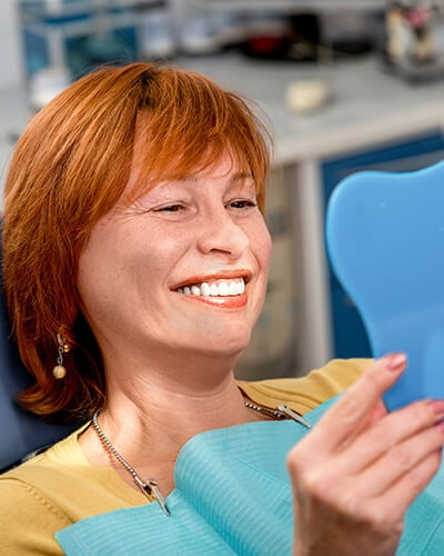 A mature woman looking at her new teeth in a blue mirror inside our Issaquah dental office
