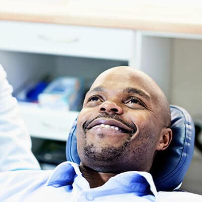 A male patient lying in the dentist's chair smiling while looking up