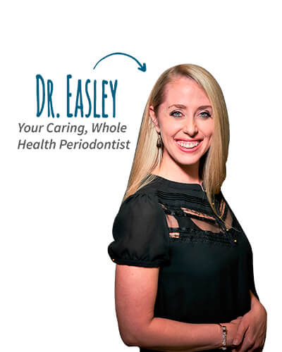 Dr. Elisabeth Easley standing smiling while wearing a black shirt and her hair is blonde and blue eyes.