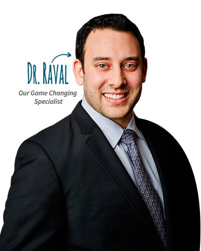 Dr. Neal Raval, our game changing specialists, standing and smiling while wearing a black suit.