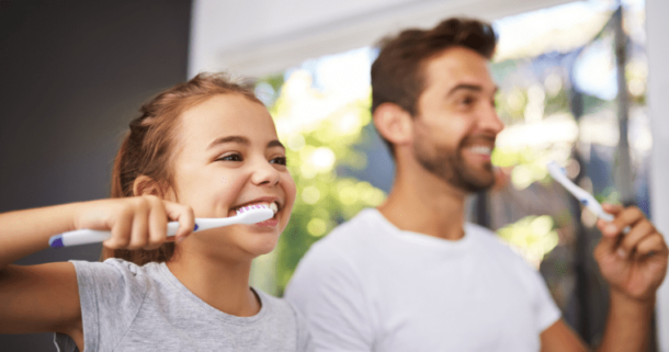 Daughter and father brushing their teeth using our dental tips during quarantine