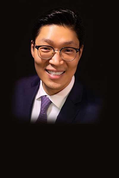 Periodontist Dr. Eddie Lee in a navy suit